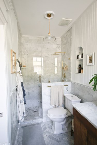 Marble tile in a shower with brass accents in farmhouse bathroom