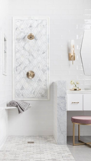 Marble tile in a shower with geometric tiles in white bathroom