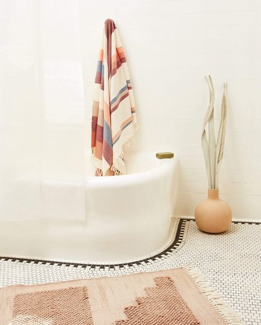 cream bathroom with tub, terra cotta bath mat, hanging towel and plant in the corner