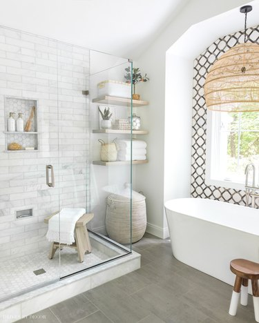 Marble tile in a shower with subway tile and hexagon floor tiles
