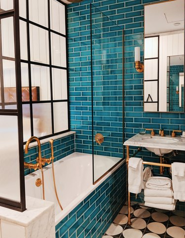 teal shower tile surrounded by iron glass shower doors