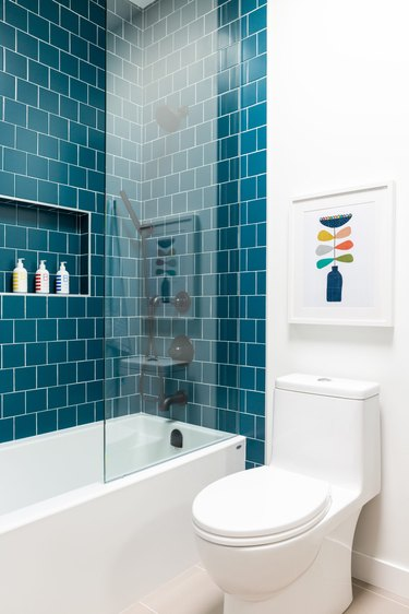 white bathroom with teal shower tile wall