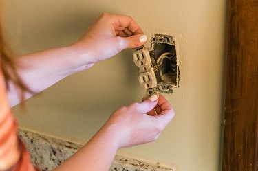 Unscrew and pull the old outlet out from the wall without entirely disconnecting it.