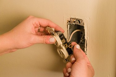 Remove the old outlet from the electrical box in the wall.