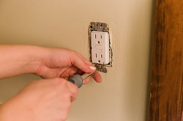 Push the outlet back inside the wall and screw it in place.