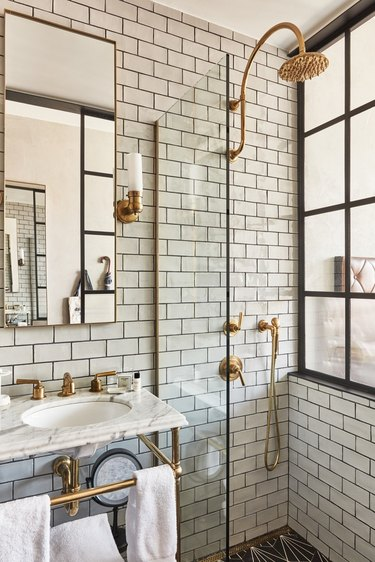 Industrial bathroom with white subway tile and brass shower fixtures