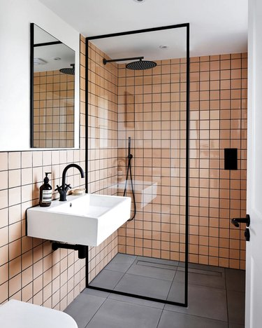 pink tiles with black grout in a modern bathroom with partitioned shower