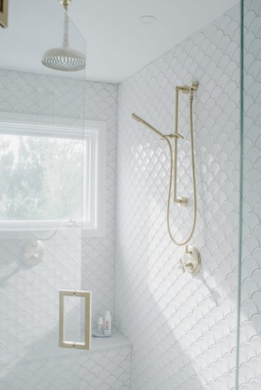 Coastal shower with white fish-scale tiles and gold fixtures