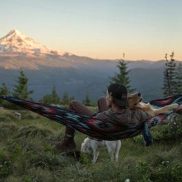 man with dog on hammock