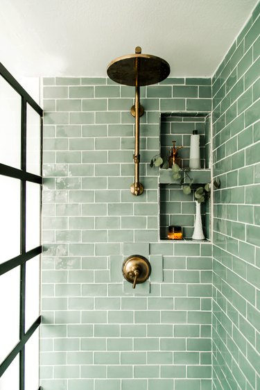 Green tile shower in light green subway tile with brass fixtures