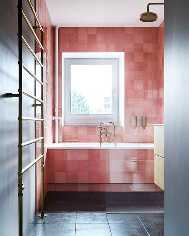 black bathroom with pink glazed tiles in the shower