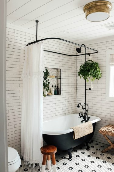 subway tiled bathroom with cast iron claw foot tub and black shower fixtures