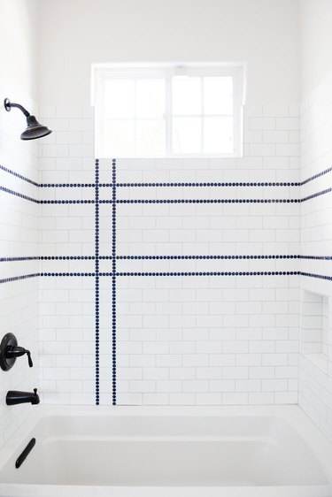 Coastal shower with white subway tile and blue tile stripes