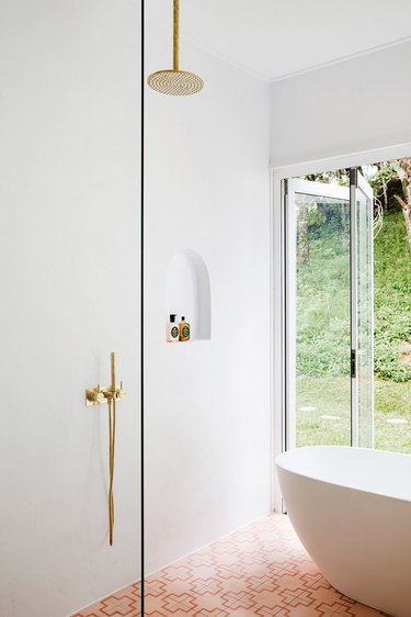 white minimalist shower with brass hardware and pink floor tiles