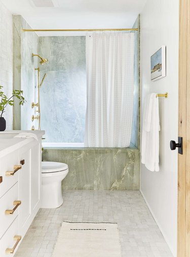 minimalist shower with green stone bath and white vanity in a white room