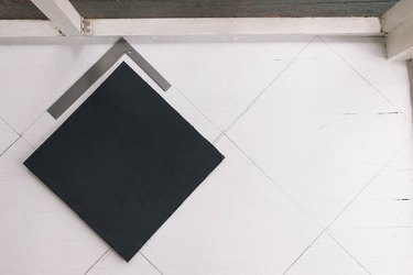 Tracing diamond pattern on floor with pencil and framing square