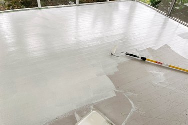 Rolling primer onto wood sunroom floor with extension pole
