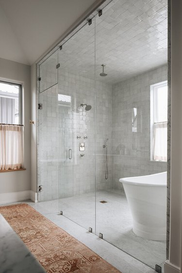 minimalist shower with glass wall to wall doors and white tiles throughout