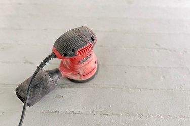 Orbital sander sanding painted wood floor