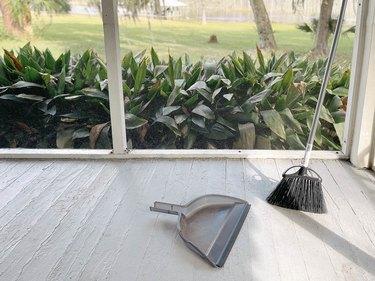 Broom and dustpan on clean sunroom floor