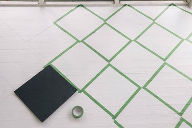 Taping diamond pattern on floor with painter's tape