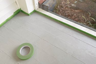 Taping painter's tape around baseboards of sunroom