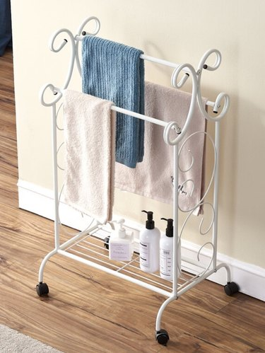 Shabby Chic Bathroom Storage with White standing towel rack with towels.