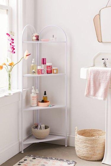 Shabby Chic Bathroom Storage in Corner bathroom shelf unit with lotions, basket, flowers, towel, sink, mirror.