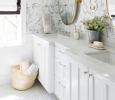Shabby Chic Bathroom Storage in Bathroom with floral wallpaper, white counter, oval mirrors, basket on floor, towels.