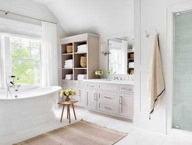 Shabby Chic Bathroom Storage in Bathroom with large tub, built in cabinets and shelves, towels, small stool, flowers, rugs.