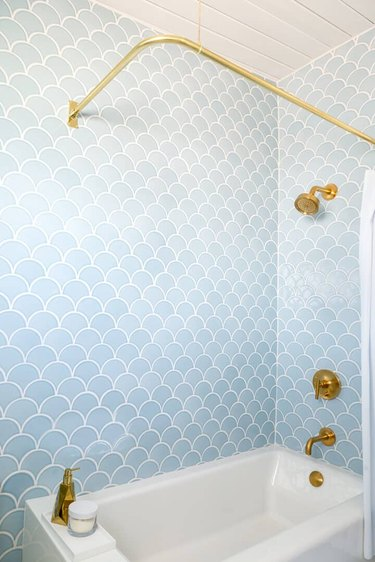 Light blue shower tile with brass accents in shower