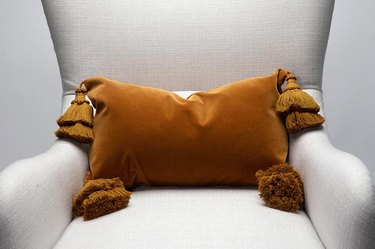 brown velvet pillow on light chair
