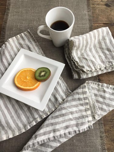 white and gray striped linen napkins with plate and mug nearby