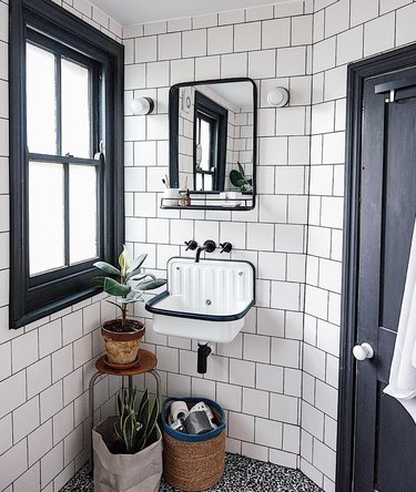 black and white small industrial bathroom with dark grout and square tile