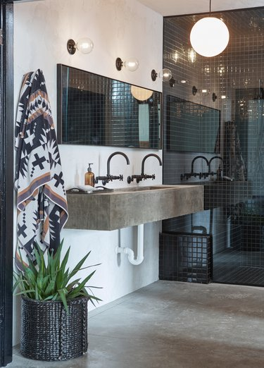 small industrial bathroom with cement sink and trio of bare bulb lights