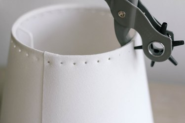 Punching holes around rim of lampshade with leather punch tool