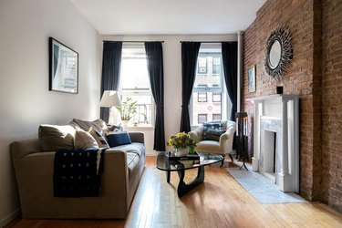 white arrow living room with fireplace, couch, brick wall, and coffee table