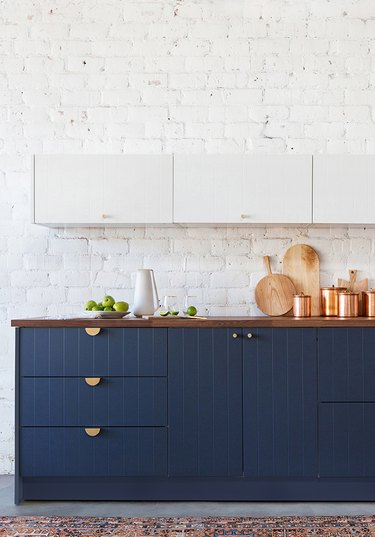 two tone kitchen with white upper cabinetry and navy blue beadboard cabinets