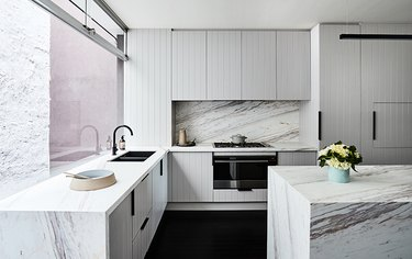 grey beadboard cabinet in kitchen with marble backsplash and island