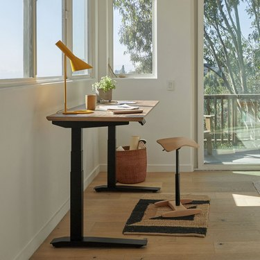 standing desk with lamp and stool near window