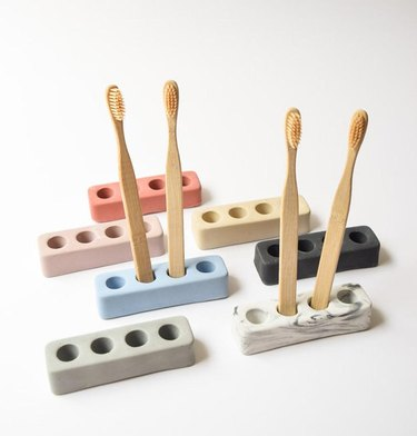Toothbrush holders in a variety of colors with wood toothbrushes