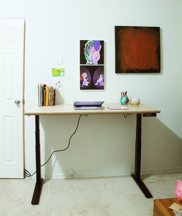 standing desk with art on the wall
