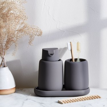 Dark gray bathroom accessories in modern bathroom with tumbler for toothbrush holder