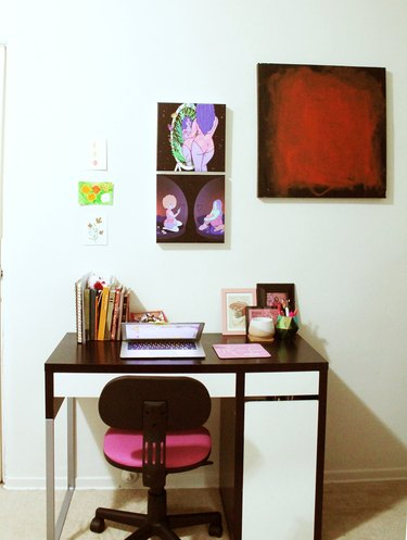 desk with pink chair and art on the wall