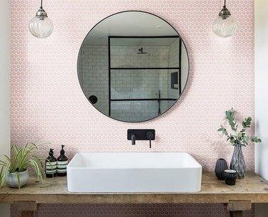 Modern rustic bathroom with white trough sink, pink hectaganol backsplash, black Wall-Mounted Bathroom Faucet, globe lamps, wood vanity.