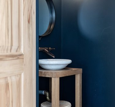 Navy bathroom with white bowl sink, brass Wall-Mounted Bathroom Faucet, round bowl sink.