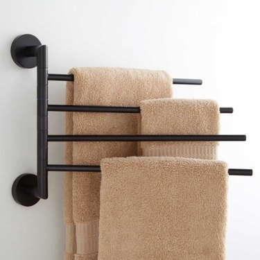 Swinging arm wall mounted black towel rack for small bathroom with brown towels
