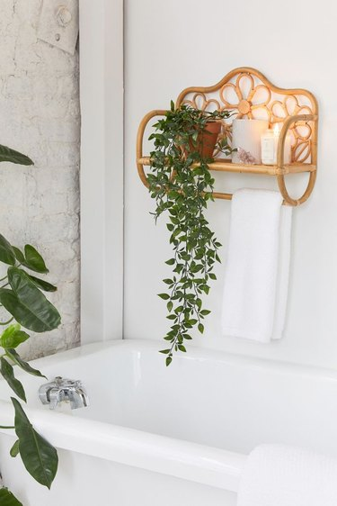 Rattan wall shelf and towel rack for small bathroom with daisy details and houseplant