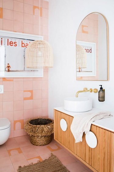 Pink bathroom with brass Wall-Mounted Bathroom Faucet, wood vanity, bowl sink, basket, cane pendant lamp, mirro.