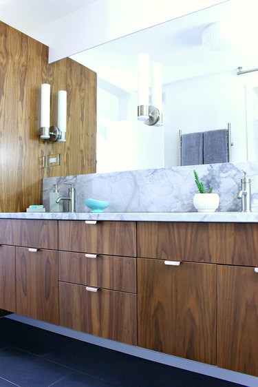 small midcentury modern bathroom with walnut cabinets and marble countertop
